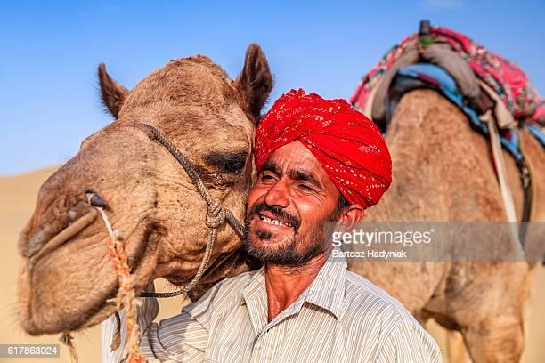 Indian man holding camel on sand dunes, Rajasthan, India