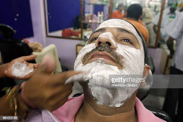 WITH 'INDIALIFESTYLECONSUMERRETAIL' Indian man Iqbal gets a layer of face cream as he receives a facial massage at a men's beauty parlour in New...