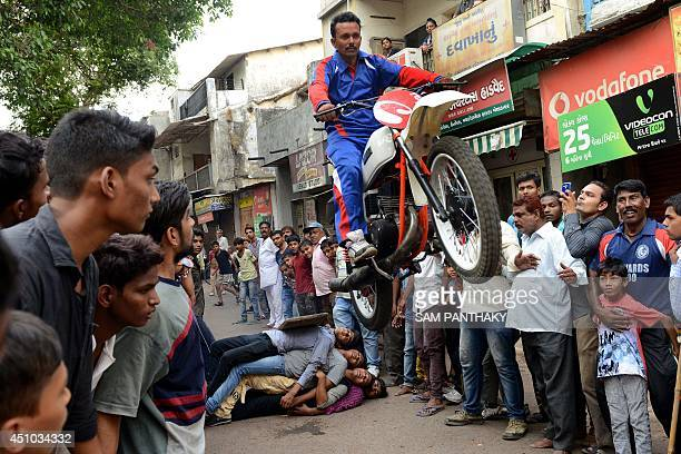 Indian man Kalpesh Modi performs with his motorcycle as he rehearses for the forthcoming annual Lord Jagannath Rath Yatra in Ahmedabad on June 22...