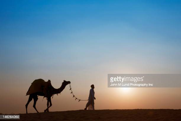 Indian man leading camel in desert