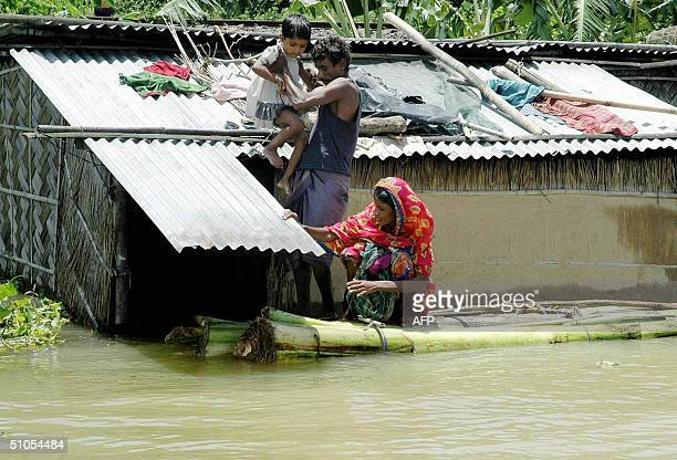 Indian man Niban Ali rescues his daughter from the roof of his submerged house in the flood affected area of Rajabari village in Kamrup district 20km...