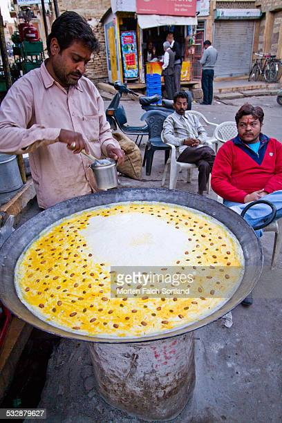 Indian man preparing a drink made from milk almonds saffron and more at a street shop in Jaisalmer