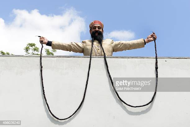 Indian man Ram Singh Chauhan displays his approximately 18 foot long moustache in Ahmedabad on September 24 2014 Ram Singh Chauhan is to be...