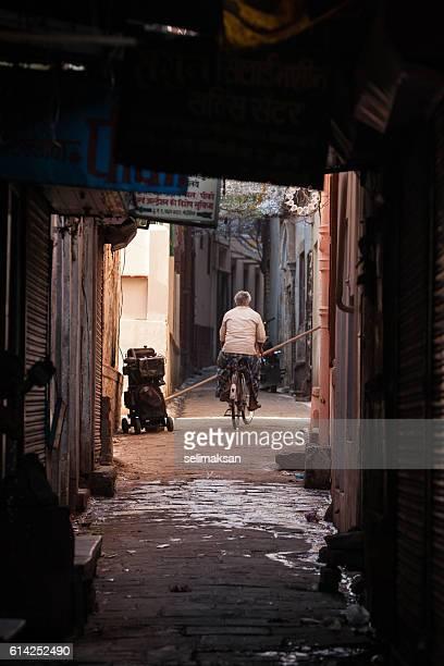 Indian man riding bike in back street of Varanasi India
