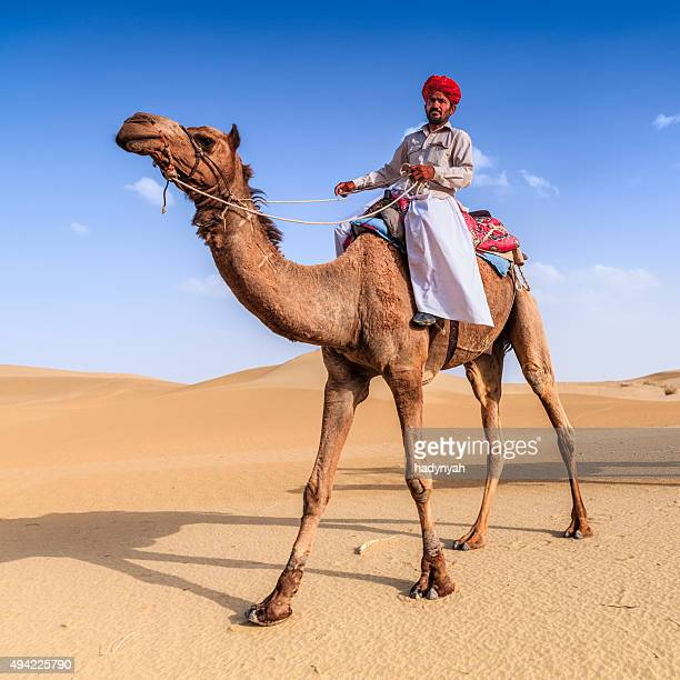 Indian man riding camel on sand dunes, Rajasthan, India