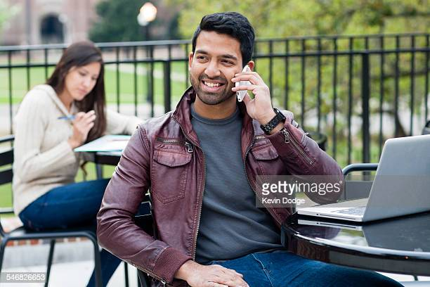 Indian man talking on cell phone at table outdoors