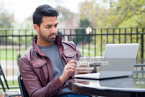 Indian man using cell phone and laptop at table outdoors