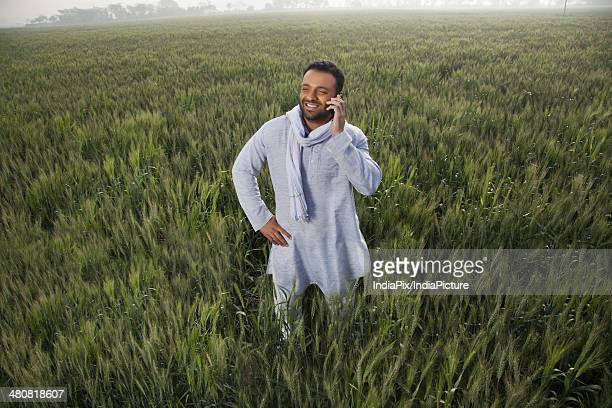Indian man using mobile phone in farm