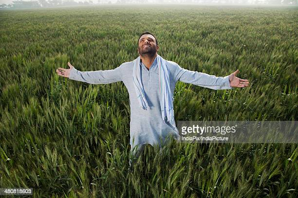 Indian man with arms outstretched standing on field