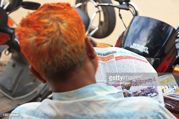 Indian man with henna died hair reading newspaper at December 18 2011 in Mysore Karnataka India