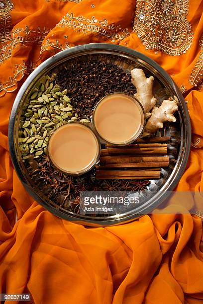 Indian masala tea with spices on silver tray.