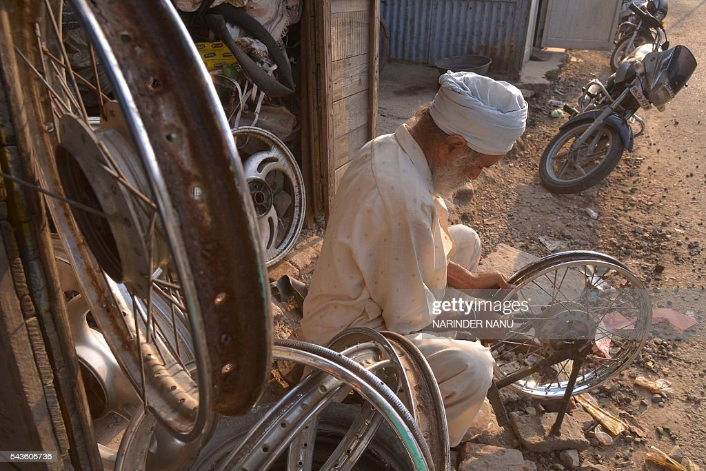 Indian mechanic, Mahinder Singh, 62, who repairs motorcycle wheels, works outside his shop in Amritsar on June 29, 2016. Singh charges INR 100 (1.50 dollars) for each motorcycle wheel repair and earns INR 200 - 300 daily. / AFP / NARINDER
