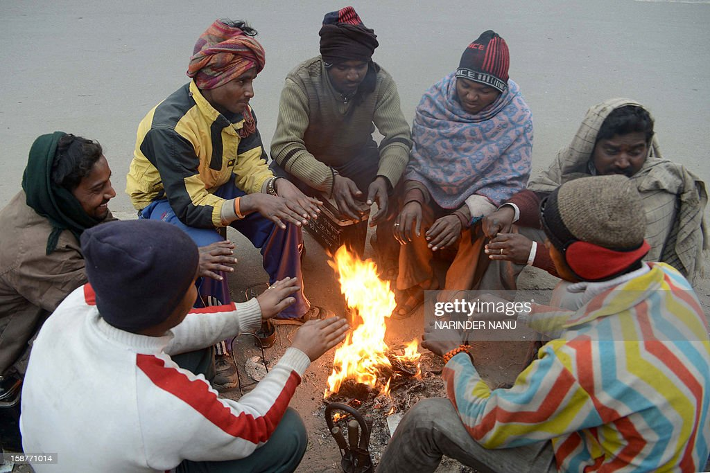 Indian mechanics warm themselves around a bonfire at a roadside in Amritsar on December 28, 2012. The northern Indian city of Amritsar faces severe cold conditions with the temperature dipping towards the 0 degree Celsius mark. AFP PHOTO/ NARINDER NANU
