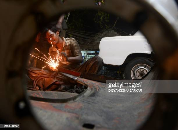 Indian mechanics works on Hindustan Motors Ambassador cars in a small roadside workshop in Kolkata on February 16 2017 One of India's most iconic car...