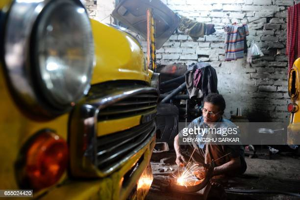 Indian mechanics works on Hindustan Motors Ambassador cars in a small roadside workshop in Kolkata on February 17 2017 One of India's most iconic car...