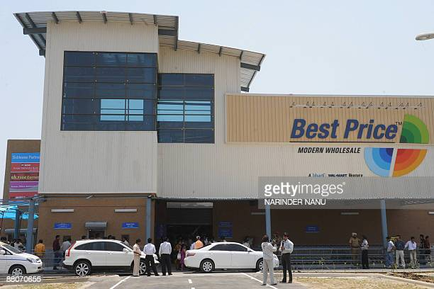 Indian media representatives stand outside the country's first ever Bharti WalMart 'Best Price' Modern Wholesale cash and carry store in the village...