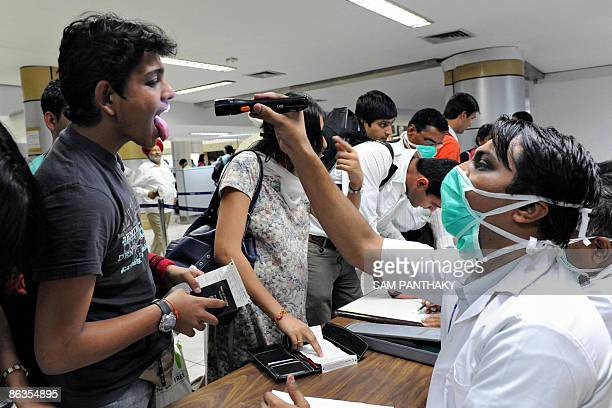 Indian medical officers screen passengers for flu symptoms following their arrival at the Sardar Vallabhbhai Patel International Airport in Ahmedabad...