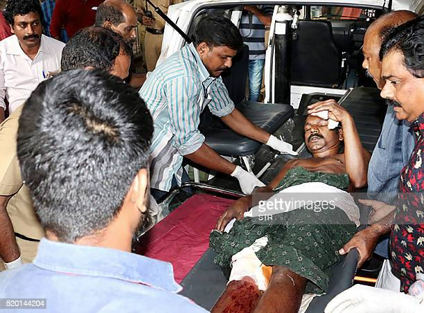 TOPSHOT Indian medical officials and bystanders carry an injured man from a vehicle into a hospital in Paravur on April 10 after an explosion and...