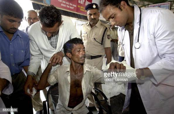 Indian medical officials attend to the injuries of Sandeep after he arrived at New Delhi Railway Station in New Delhi 29 July 2005 after he was...