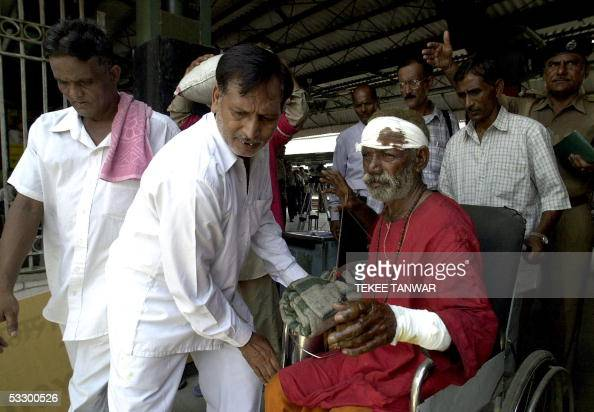 Indian medical officials use a wheel chair to assist Shiv Mandir Pathak to hospital at New Delhi Railway Station in New Delhi 29 July 2005 after he...