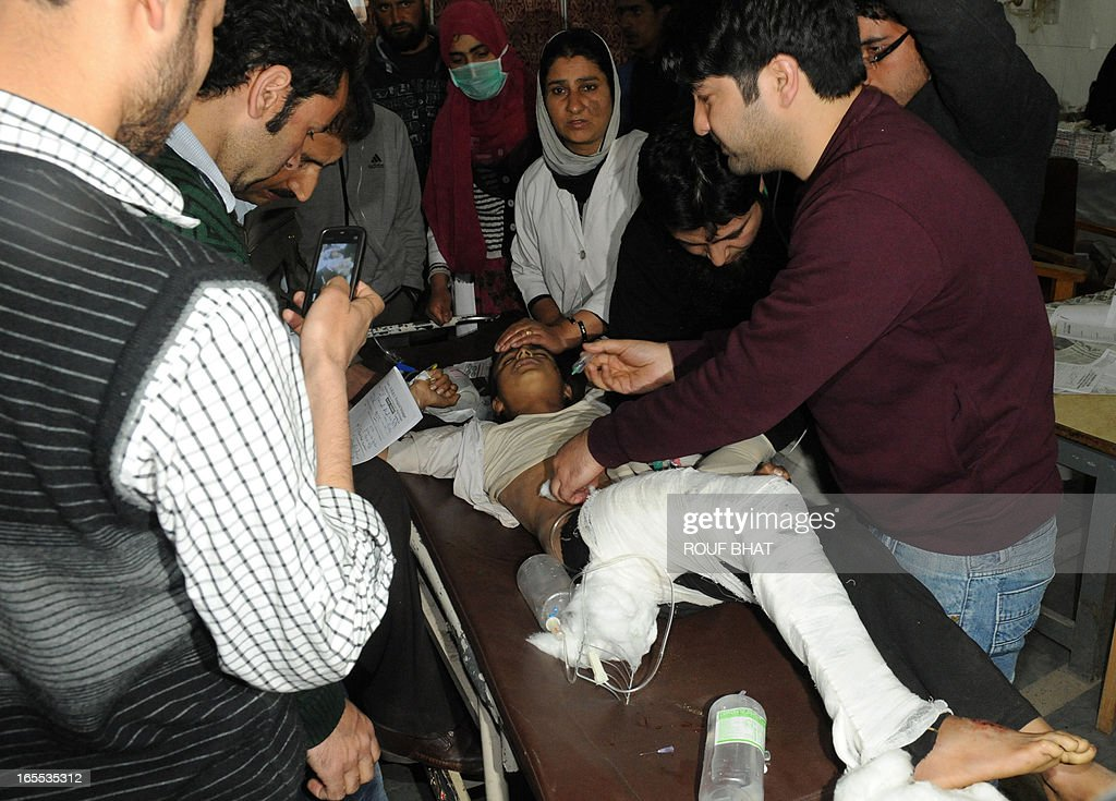 Indian medical staff and volunteers treat an injured student on a stretcher at a hospital in Srinagar on April 4,2013. Eight students were killed and nine others injured when a school bus skidded off a mountain road and fell into a 300-feet gorge in Anantnag district of south Kashmir official said. AFP PHOTO/ Rouf BHAT