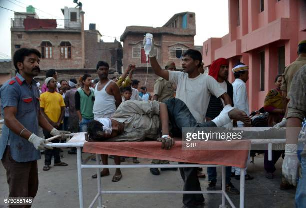 Indian medical staff and volunteers use a trolley to move an injured bus passenger into a hospital in Etah some 35kms south of Agra on May 5 after a...