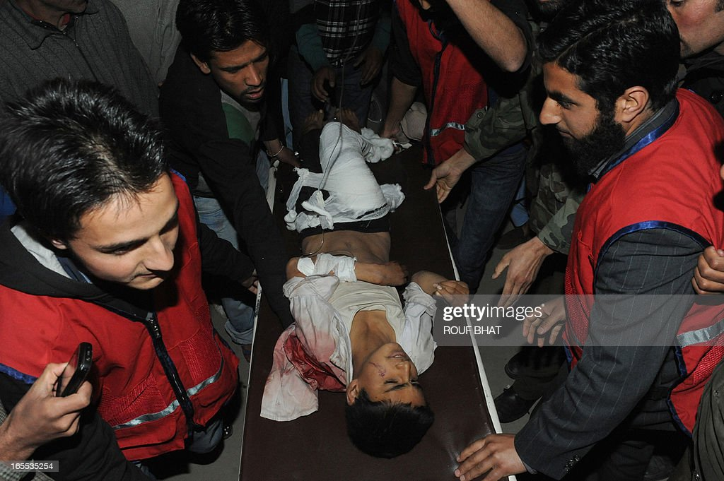 Indian medical staff and volunteers wheel an injured student on a stretcher to a hospital in Srinagar on April 4,2013. Eight students were killed and nine others injured when a school bus skidded off a mountain road and fell into a 300-feet gorge in Anantnag district of south Kashmir official said. AFP PHOTO/ Rouf BHAT