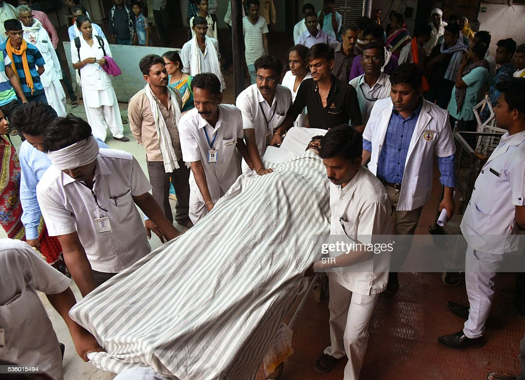 Indian medical staff bring a man injured in a fire to hospital in Wardha some 100kms from Nagpur on May 31, 2016. A massive fire that erupted at one of India's largest military ammunition depots May 31 killed at least 16 soldiers and firefighters, reigniting safety concerns about military equipment and installations. The blaze broke out in the early hours at the high-security facility which stores bombs, grenades and other ordnance outside the central city of Pulgaon. Flames lit up the night sky. / AFP / STR