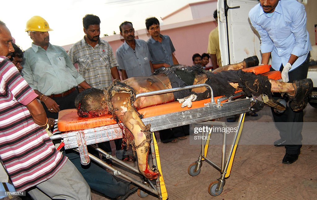 Indian medical staff use a trolley to move the body of a worker into the mortuary of the KG Hospital in Visakhapatnam on August 23, 2013, after his death in an industrial accident at the Hindustan Petroleum Corp refinery in the coastal city. A massive fire broke out at a petroleum refinery in southern India, killing four workers and leaving dozens injured, police said. Another 11 people were feared trapped at the Hindustan Petroleum Corp refinery in Visakhapatnam, a port city some 503 kilometres (313 miles) from Andhra Pradesh state capital Hyderabad, officials added. AFP PHOTO/STR