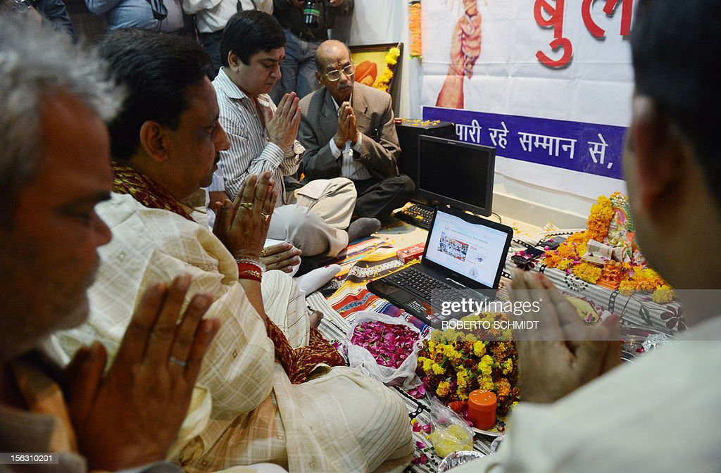 Indian members of a local trading organization celebrate Diwali by chanting mantras as they worship electronic gadgets including iPads,laptops and mobile phones on Diwali, the Festival of Lights at their office in New Delhi on November 13, 2012. Since ages, the worshipping of account books has been an essential part of Diwali for the business community in India for prosperity of business. Signifying the modernisation of the retail trade in India, some traders are now including the worshipping of electronic gadgets. The festival of Diwali celebrates the victory of good over evil, light over darkness and knowledge over ignorance. AFP PHOTO/Roberto Schmidt