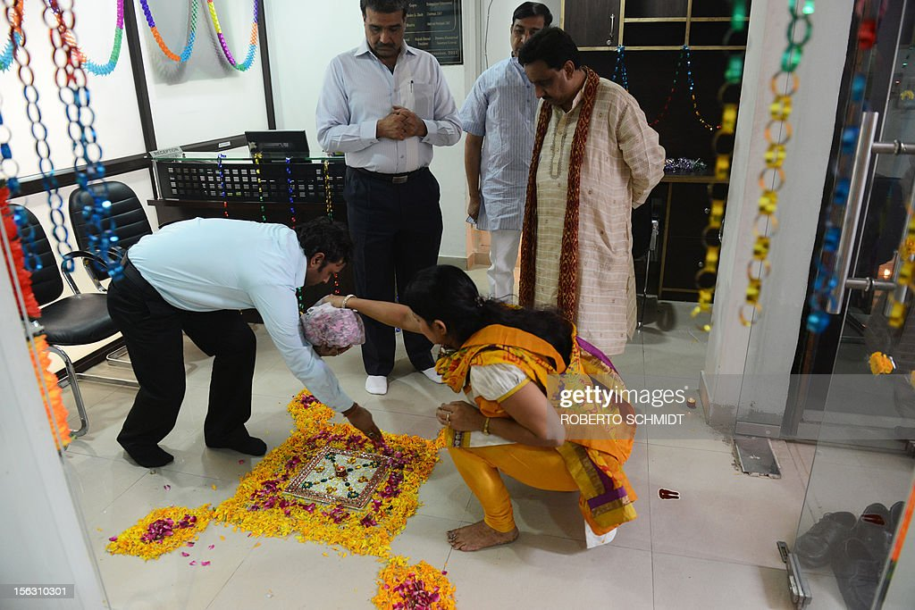 Indian members of a local trading organization put the final touches to a flower petal decoration on the floor of their office before they participate in a ceremony in which they worship electronic gadgets including iPads, laptops and mobile phones on Diwali, the Festival of Lights at their office in New Delhi on November 13, 2012. Since ages, the worshipping of account books has been an essential part of Diwali for the business community in India for prosperity of business. Signifying the modernisation of the retail trade in India, some traders are now including the worshipping of electronic gadgets. The festival of Diwali celebrates the victory of good over evil, light over darkness and knowledge over ignorance. AFP PHOTO/Roberto Schmidt