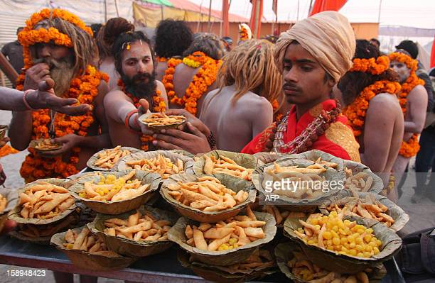 Indian members of Akhara distribute food to Indian Hindu Saddhus after a religious procession of the first 'royal entry' of the Kumbh Mela at the...