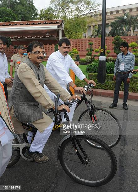 Indian Members of Parliament Tarun Vijay and D Kumar head to parliament on bicycles to raise awareness on health and pollution issues in New Delhi on...