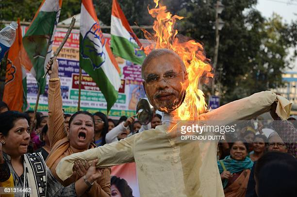 Indian members of the Congress Party burn an effigy of Prime Minister Narendra Modi during a protest against demonetisation in Siliguri on January 9...
