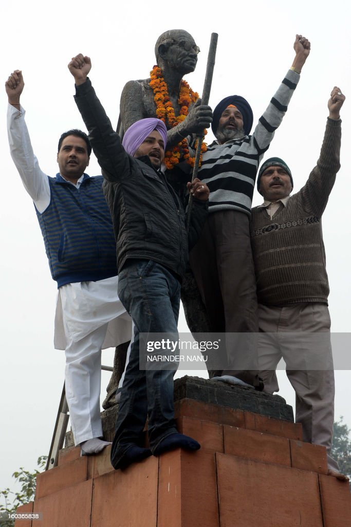 Indian members of the Congress Party shout slogans after placing garlands on a statue of Mahatma Gandhi, on Martyrs Day in Amritsar on January 30, 2013, the 65th anniversary of Gandhi's assassination. Mahatma Gandhi was on the way to a prayer meeting in the Indian capital when he was shot three times in the chest and head on January 30, 1948.