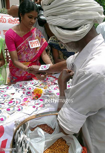 Indian members of the Democratic Youth Federation India tie 'rakhis' carrying a message of peace and unity onto the wrists of passersby in Hyderabad...