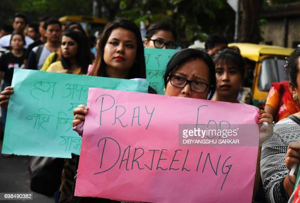 Indian members of the Gorkha community and students hold placards during a protest in support of the Gorkhaland movement in Kolkata on June 20 2017...
