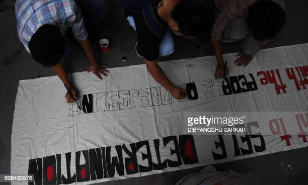 Indian members of the Gorkha community and students prepare a banner during a protest in support of the Gorkhaland movement in Kolkata on June 20...