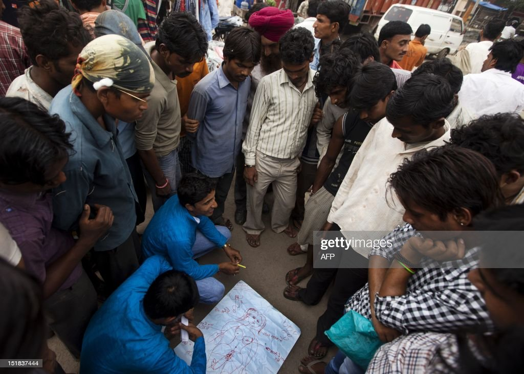Indian members of the NGO Child Survival India draw a female body to help Indian truck drivers understand sex and the human body during an HIV prevention and effects outreach program at Sanjay Gandhi Transport Nagar, a transport rest area in New Delhi on August 25, 2012. Truckers spend as much as 67 per cent of their time on the road trying to maximize their earnings, and average 4000 INR (72 USD) a month. At the Transport Nagar there are over 2500 trucks parked at any moment, and approximately five million truck drivers and helpers travel the 66,000 km of national highways in India. One third of truckers report commercial sex and truckers are an estimated 10-12 per cent of clients of sex workers. HIV prevalence among long-distance truckers ranges from three to seven per cent, and one to seven per cent have at least one sexually transmitted disease (STD). NGO's like Child Survival India work with truckers to educate them on safe sex practices, condom use, and offer clinics for STD treatments. AFP PHOTO/ Andrew Caballero-Reynolds