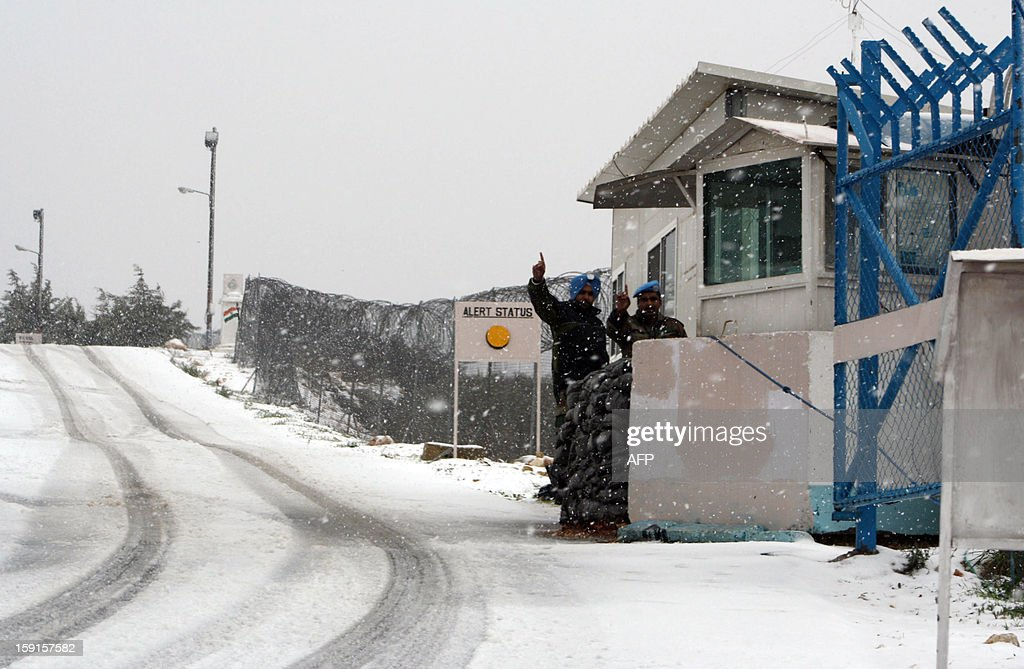 Indian members of the United Nations Interim Force in Lebanon gesture as they stand outside a guard house as snow falls in the southern town of Marjaoun on January 9, 2013, as stormy weather sparked widespread flooding, prompting chaos on the roads and a nationwide school closure. AFP PHOTO/ALI DIA