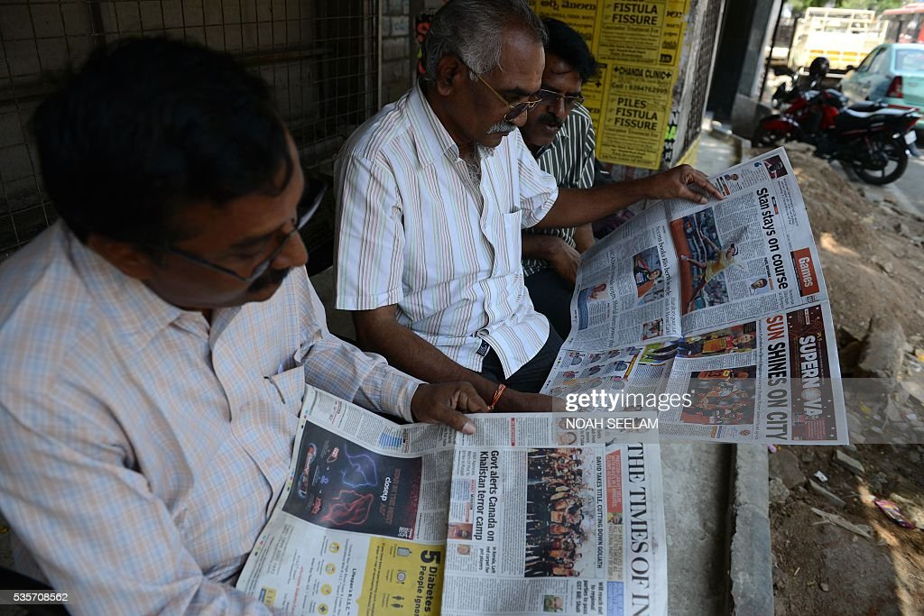 Indian men brows newspapers featuring front-page coverage of the Sunrisers Hyderabad team winning the trophy of 2016 Indian Premier League (IPL) Twenty20 cricket match against Royal Challengers Bangalore in Hyderabad, on May 30, 2016. / AFP / NOAH