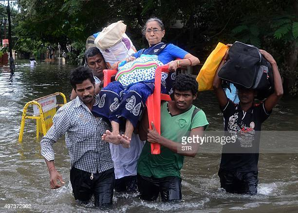 Indian men carry an elderly woman on a flooded street following heavy rain in Chennai on November 16 2015 Large areas of the southern Indian city of...