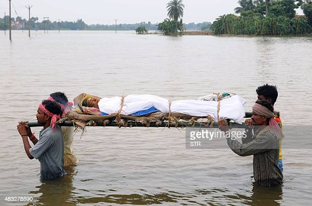 Indian men carry the body of a woman killed in the flooding as they walk through an inundated area near Faridpur village in Hooghly district in West...