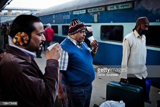 Indian men drink chai tea on the platform prior to departing from the Nizamuddin Railway Station on February 07 2012 in New Delhi India The...