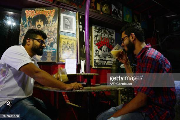 Indian men drink coffee in beer mugs at Pecos one of Bangalore's oldest pubs on July 4 in the wake of the Supreme Court's ban on selling alcohol near...