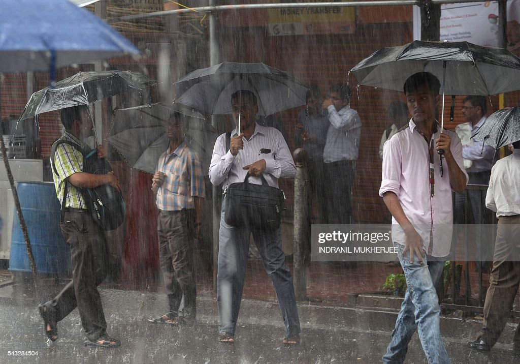 Indian men hold umbrellas under heavy rain in Mumbai on June 27, 2016. Annual monsoon rains have progressed to most parts of western and central India, easing fears of millions of desperate farmers after two straight years of drought, the weather department said. / AFP / INDRANIL