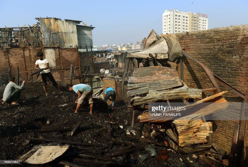 Indian men look for their belongings after a fire raged through the Nayanagar slum in Mumbai on January 25, 2013. A fire killed six people when it ripped through a slum in the heart of Mumbai on January 25 and left hundreds homeless, emergency services said.