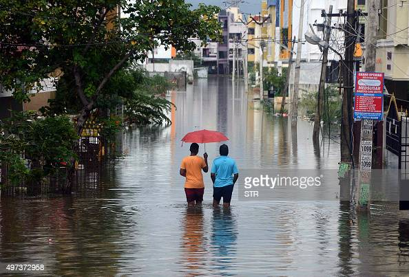 Indian men make their way on a flooded street following heavy rain in Chennai on November 16 2015 Large areas of the southern Indian city of Chennai...