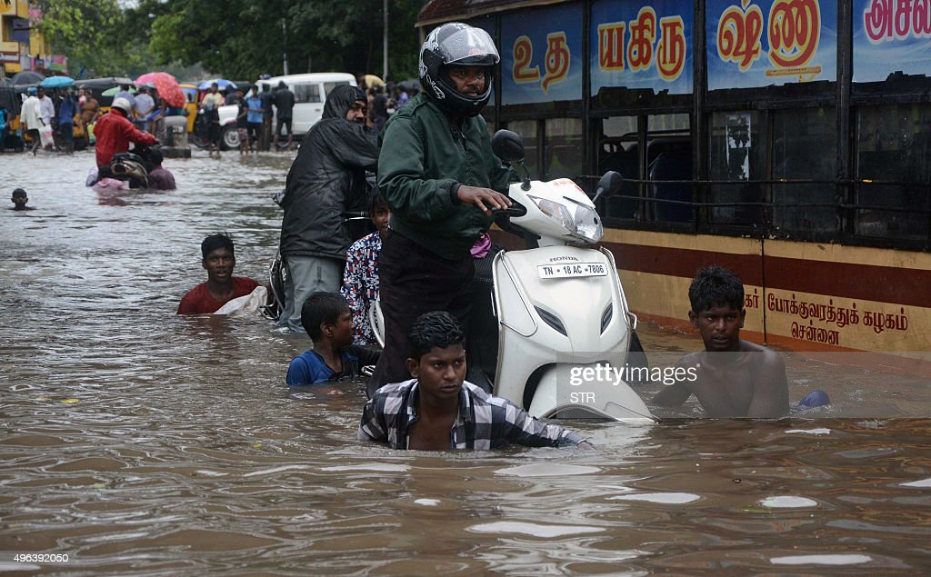 Indian men make their way on a flooded street in Chennai on November 9 2015 following heavy rain from an approaching cyclonic system off the coast...
