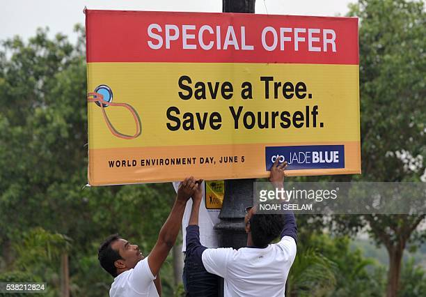 Indian men put up a board prior to a rally on World Environment Day in Hyderabad on June 5 2016 World Environment Day is observed every year on June...